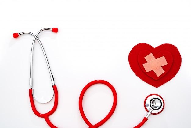 Dia mundial da saúde, cuidados de saúde e conceito médico, estetoscópio vermelho e coração vermelho sobre fundo branco