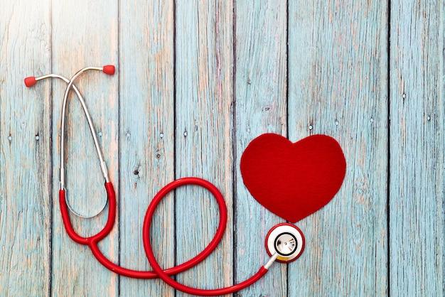 Dia mundial da saúde, cuidados de saúde e conceito médico, estetoscópio vermelho e coração vermelho sobre o fundo azul de madeira