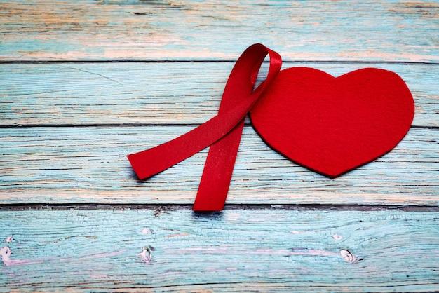 Dia mundial da saúde, cuidados de saúde e conceito médico, fita vermelha e coração vermelho sobre o fundo azul de madeira