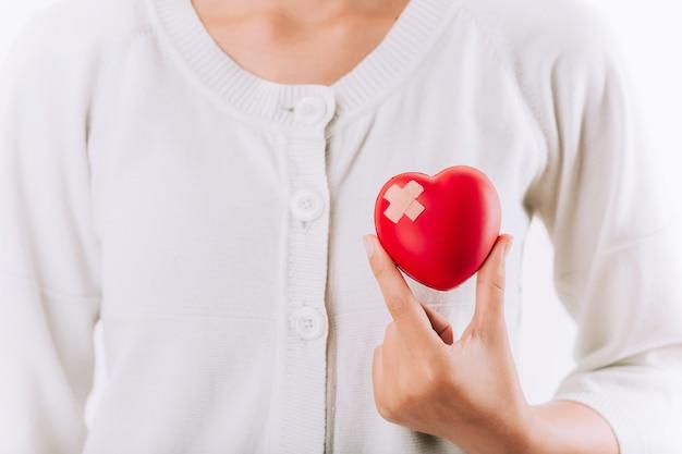 Dia mundial da saúde, cuidados de saúde e conceito médico. mulher segurando um coração vermelho com bandagem nas mãos