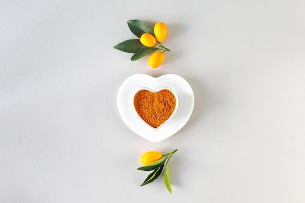 Dia mundial da saúde. cúrcuma em um prato em forma de coração. conceito de comida saudável, vista superior.