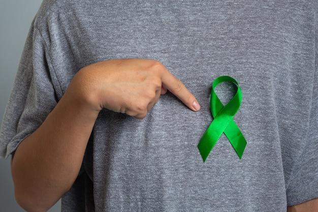 Dia mundial da saúde mental. mão apontando para fita verde