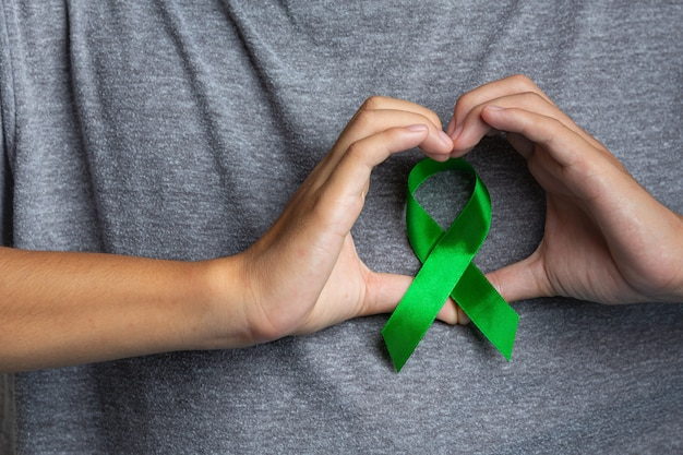 Dia mundial da saúde mental. mão do homem em forma de coração em volta de uma fita verde