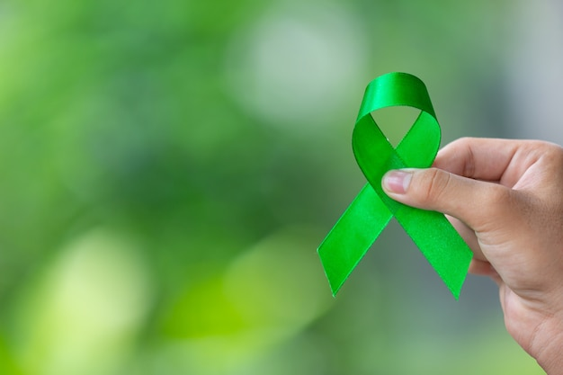 Dia mundial da saúde mental. mão segurando fita verde