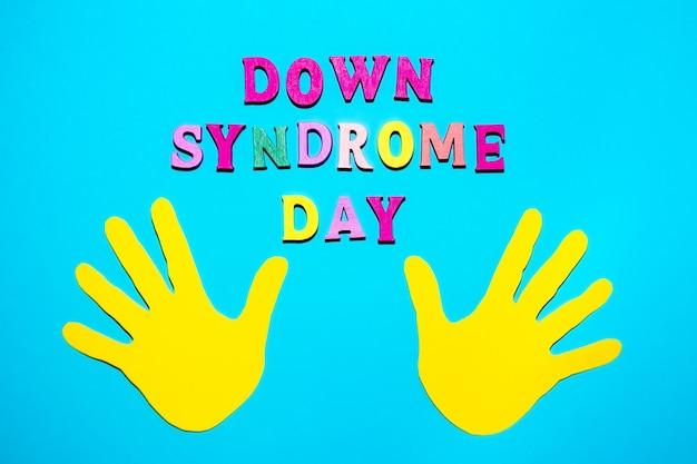 Dia mundial da síndrome de down - inscrição disposta a partir de letras de madeira sobre fundo azul e amarelo nas palmas das mãos. conceito de conscientização da síndrome de down. banner, ilustração, pôster.