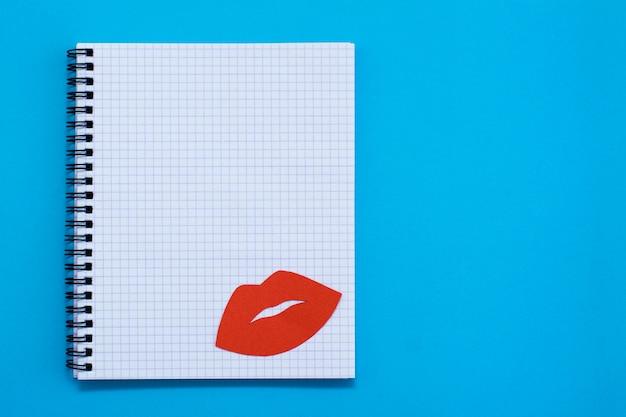 Dia mundial do beijo. lábios vermelhos em uma folha em branco do caderno aberto sobre um fundo azul