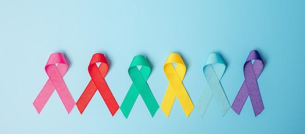 Dia mundial do câncer (4 de fevereiro). fitas coloridas de conscientização; cor azul, vermelha, verde-azulada, rosa, roxa e amarela sobre fundo de madeira para apoiar as pessoas que vivem e doenças. conceito de saúde e medicina