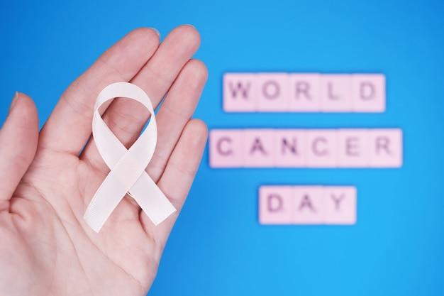 Dia mundial do câncer, 4 de fevereiro. mulher segurando fita rosa na mão