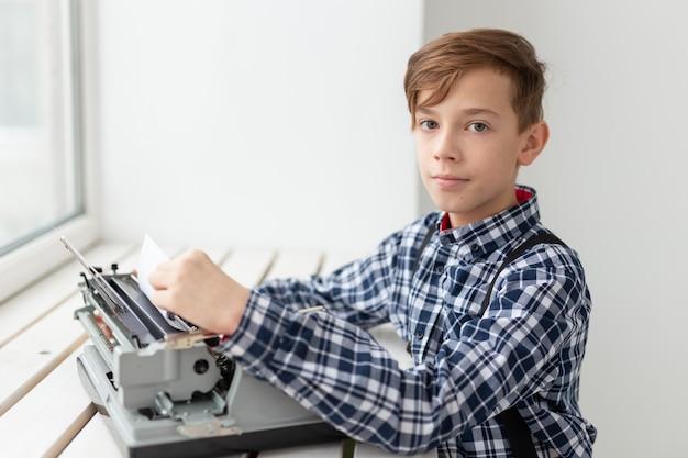 Dia mundial do conceito do escritor - menino com uma velha máquina de escrever