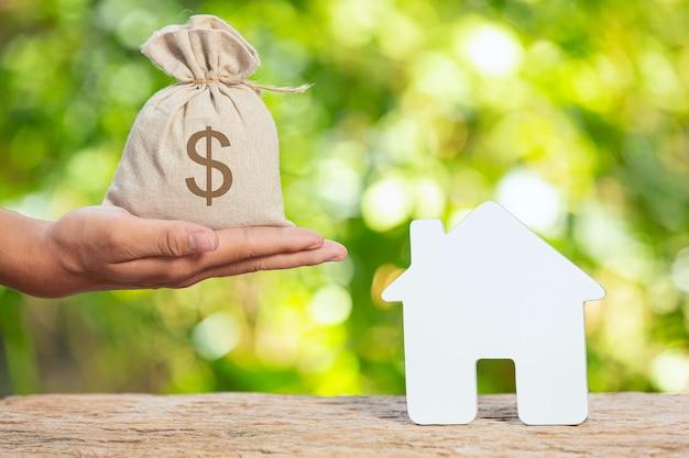 Dia mundial do habitat, foto em close de um saco de moedas e uma casa modelo