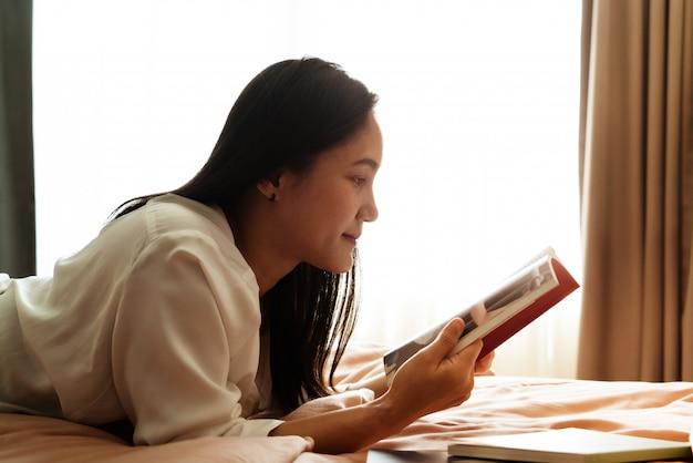 Dia mundial do livro, a mulher deita na cama lendo o livro em branco