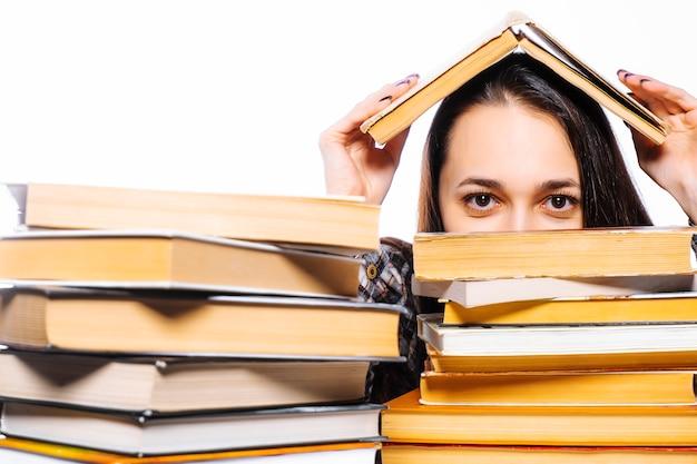 Dia mundial do livro e direitos autorais. a mulher está se escondendo atrás de livros.