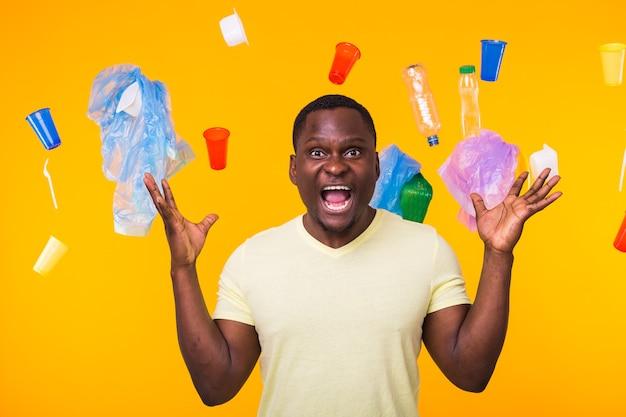 Dia mundial do meio ambiente, problema de reciclagem de plástico e conceito de desastre ambiental - homem apavorado na parede amarela com lixo.