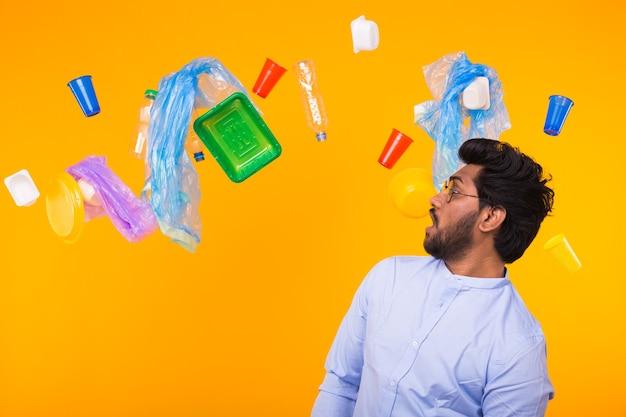Dia mundial do meio ambiente, problema de reciclagem de plástico e conceito de desastre ambiental - homem indiano surpreso olhando para o lixo na parede amarela.