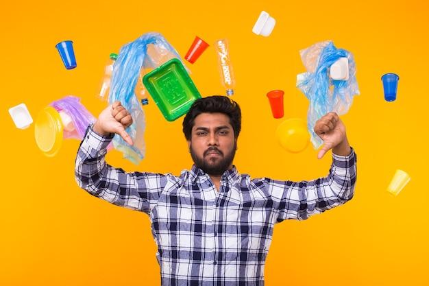 Dia mundial do meio ambiente, problema de reciclagem de plástico e conceito de desastre ambiental - triste homem indiano dando polegares para baixo