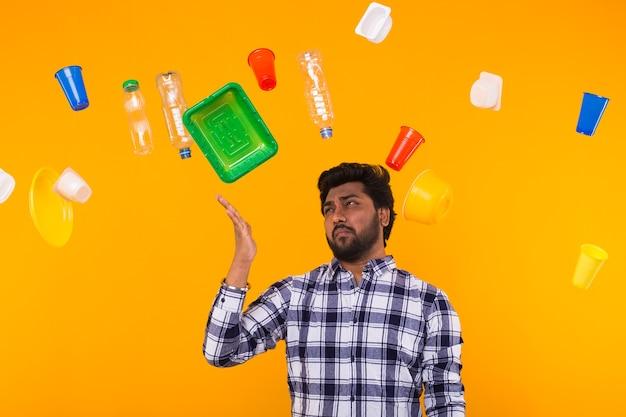 Dia mundial do meio ambiente, problema de reciclagem de plástico e conceito de desastre ambiental - triste homem indiano olhando para o lixo