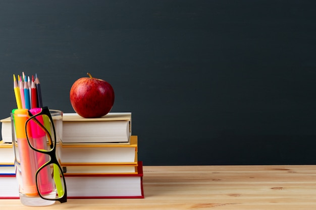 Dia mundial do professor, maçã e livros com lápis e óculos na mesa na sala de aula.