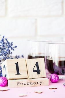 Dia mundial dos namorados. calendário de madeira com data de 14 de fevereiro em fundo rosa com café e doces