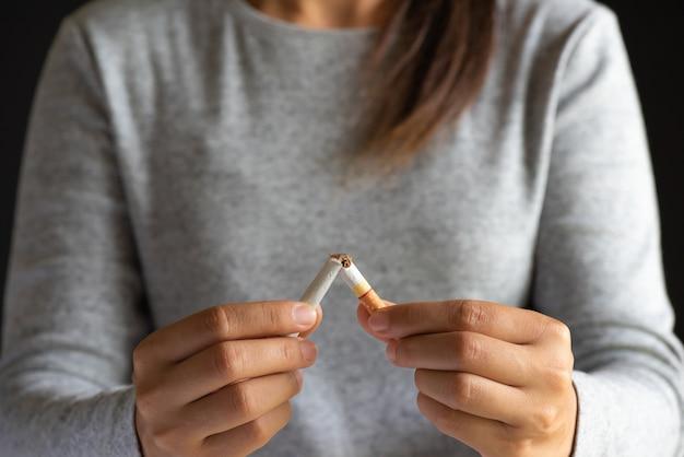 Dia mundial sem tabaco, close-up mulher mão quebrando cigarros