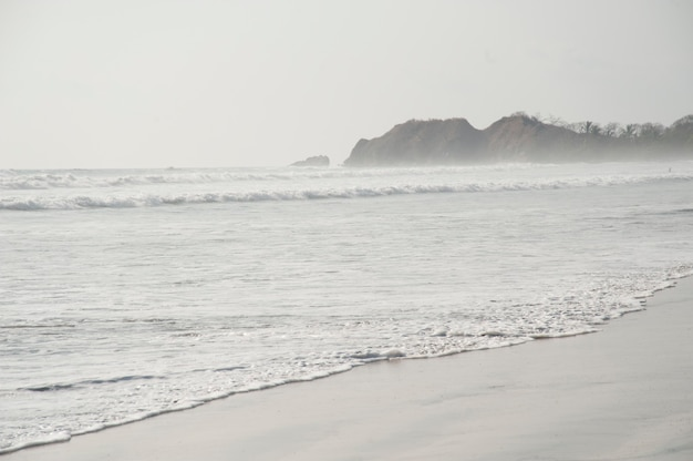 Dia nublado à beira-mar com ondas lambendo contra a praia