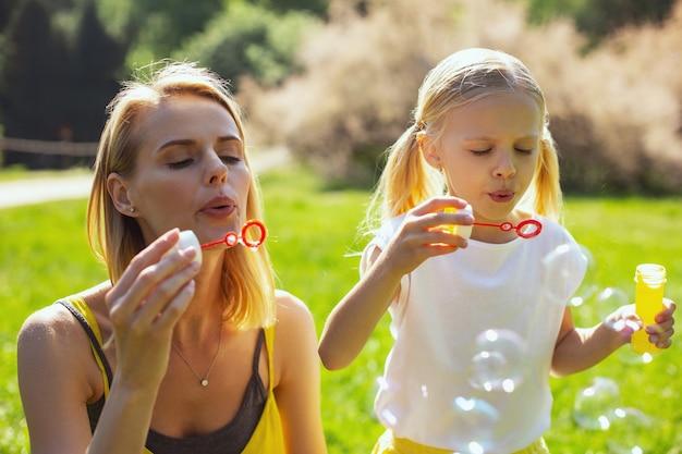 Dia perfeito. mãe atenciosa determinada soprando bolhas de sabão com a filha enquanto se diverte no parque