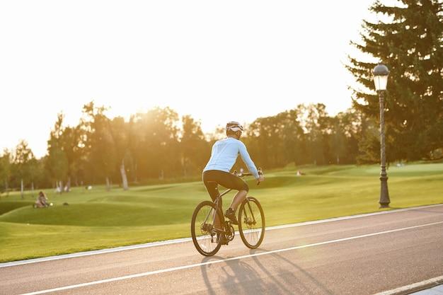 Dia perfeito para andar de bicicleta, retrovisor de um homem atlético em roupas esportivas andando de bicicleta ao longo do