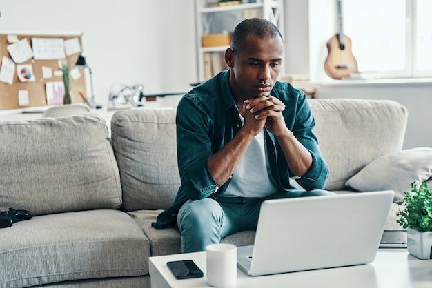 Dia preguiçoso em casa. africano jovem e bonito usando um laptop enquanto está sentado dentro de casa