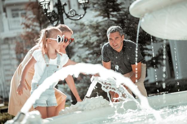 Dia quente de verão. menina concentrada usando grandes óculos escuros, refrescando-se junto com seus pais perto da grande fonte.
