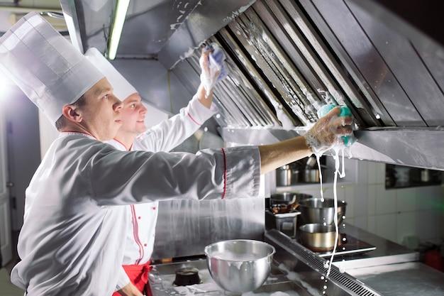 Dia sanitário no restaurante. cozinheiros lavar forno, fogão e exaustor no restaurante.