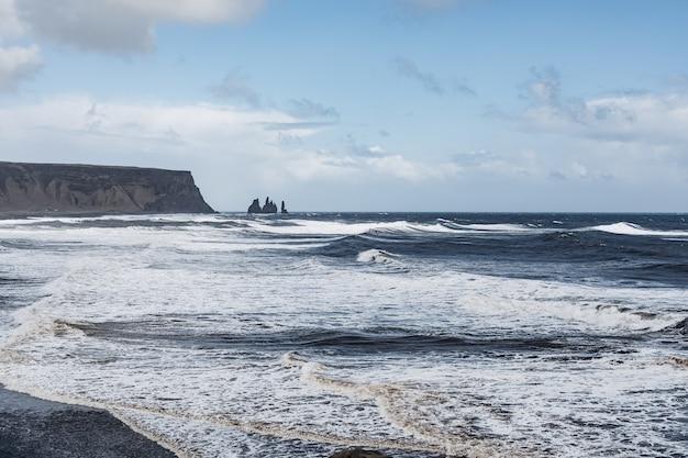 Dia tempestuoso e sombrio na praia de areia preta reynisfjara, no sul da islândia, europa, ondas enormes em