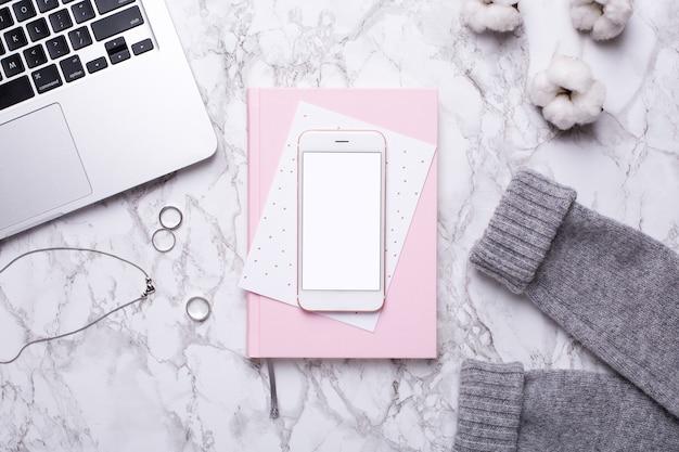 Dia útil da mulher com telefone celular, teclado e caderno rosa na mesa de mármore