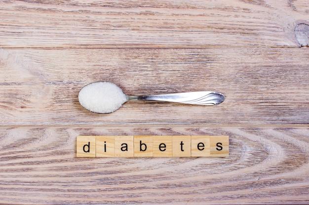 Diabetes bloquear letras de madeira e pilha de açúcar em uma colher
