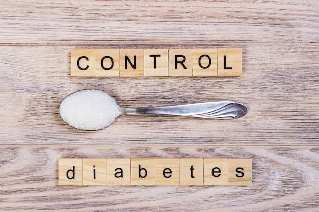 Diabetes controle bloco letras de madeira e pilha de açúcar em uma colher