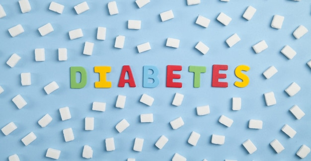 Diabetes de palavra colorida e cubos de açúcar sobre fundo azul.