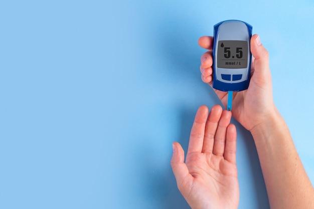Diabético usando medidor de glicose para medir o nível de glicose no sangue.