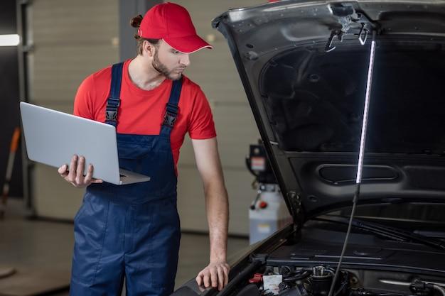 Diagnóstico do carro. jovem barbudo de boné e macacão com laptop na mão, verificando atentamente a anatomia do carro na oficina