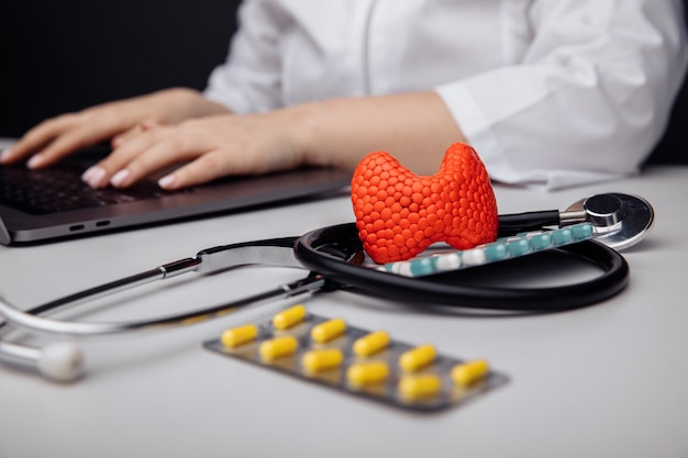 Diagnóstico precoce e tratamento da tireoide em primeiro plano é um modelo de glândula tireoide perto do estetoscópio na mesa ao fundo