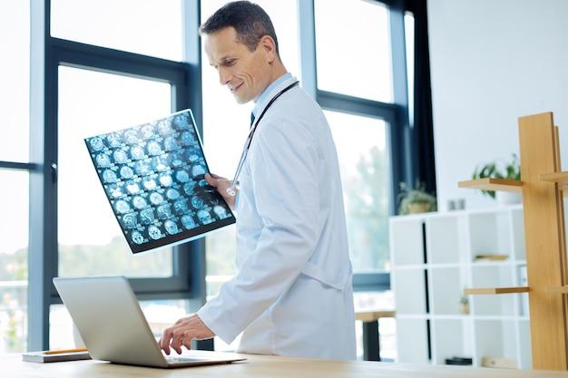 Diagnósticos médicos. radiologista sério e inteligente segurando uma radiografia e pressionando um botão em seu laptop enquanto está no escritório