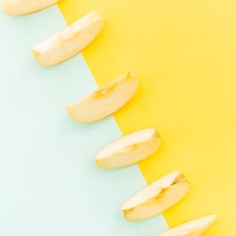 Diagonal de fatias de maçãs em fundo colorido