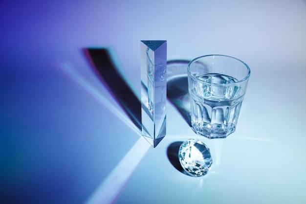 Diamante cintilante; prisma; copo de água com sombra no fundo azul escuro