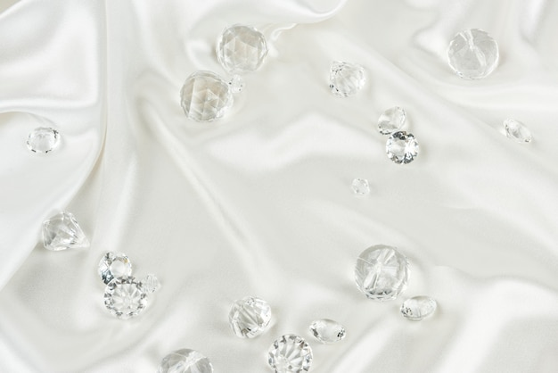 Diamantes transparentes decorativos em fundo de tecido branco texturizado