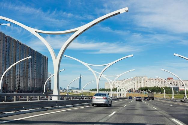 Diâmetro da via expressa ocidental da rodovia em um dia ensolarado, grande edifício à esquerda e a torre lakhta center à distância - são petersburgo, rússia, junho de 2021.