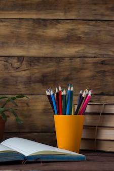 Diário aberto, uma pilha de livros, lápis de cor em um copo de plástico, flor em uma panela em um fundo de madeira