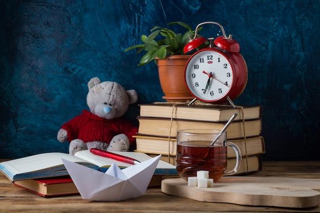 Diário aberto, uma pilha de livros, uma caneta. o conceito de aprender conhecimento