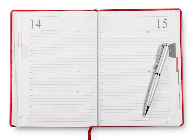 Diário aberto vermelho com caneta