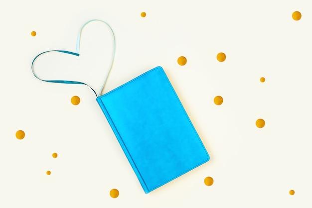 Diário azul e rodadas douradas. sobre um fundo claro. marcadores em forma de coração.
