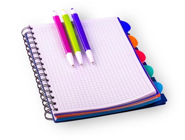 Diário (caderno) e canetas coloridas isoladas.