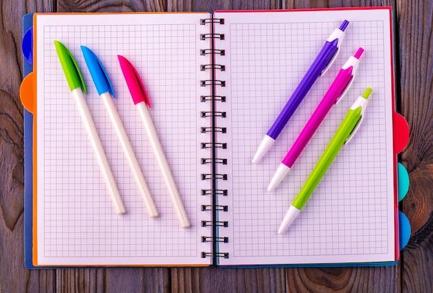 Diário (caderno) e canetas coloridas na mesa de madeira.