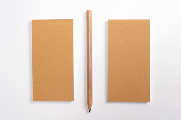 Diário com capa dura de papelão em branco e lápis de madeira isolado no branco.
