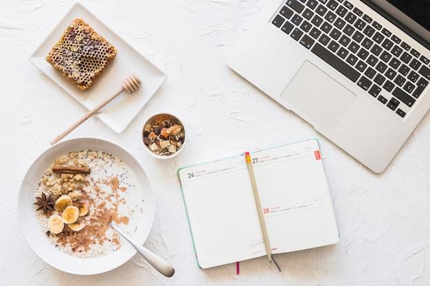 Diário com lápis; computador portátil; e saudável café da manhã no cenário áspero